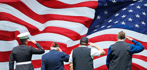 Four men standing in front of flag saluting